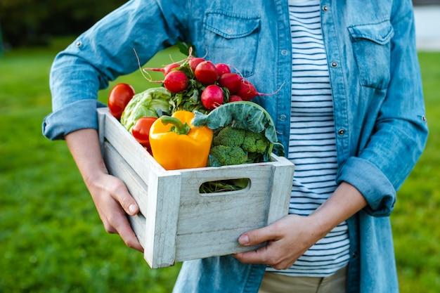 日没時の新鮮な生態野菜の箱を持つ若い女性