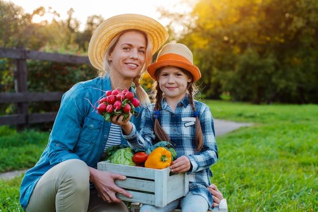 農家の母と子は野菜の箱を保持します