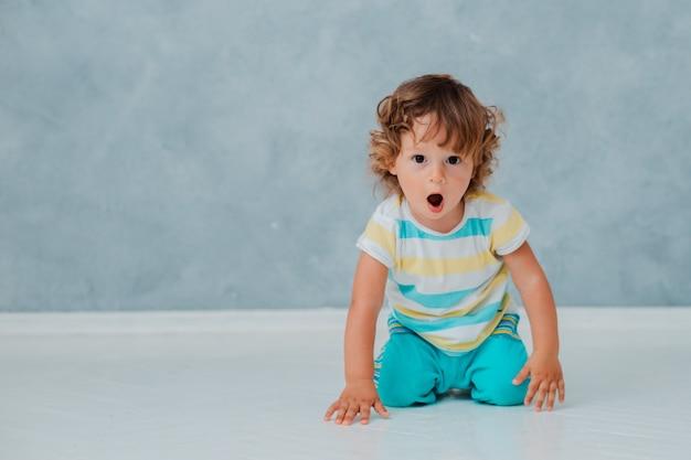 面白いかわいい巻き毛の幼児は、灰色の壁の背景に白い床に車で遊んで座っています。