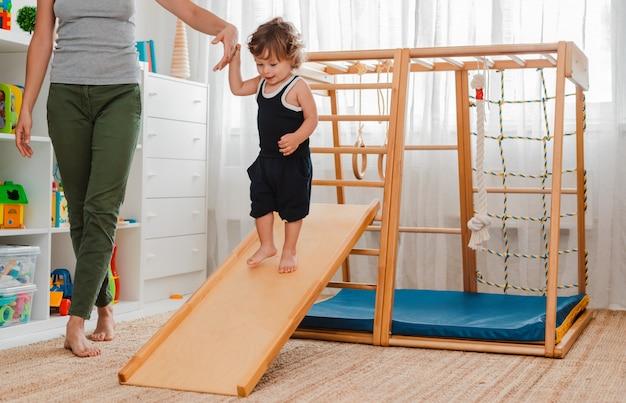 Ребенок в раннем возрасте занимается в детском доме деревянным спортивным комплексом.