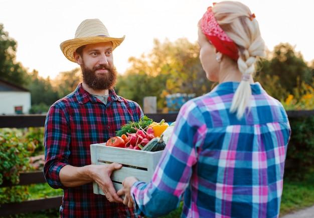 Мужчина и женщина держат ящик с урожаем сельскохозяйственных овощей
