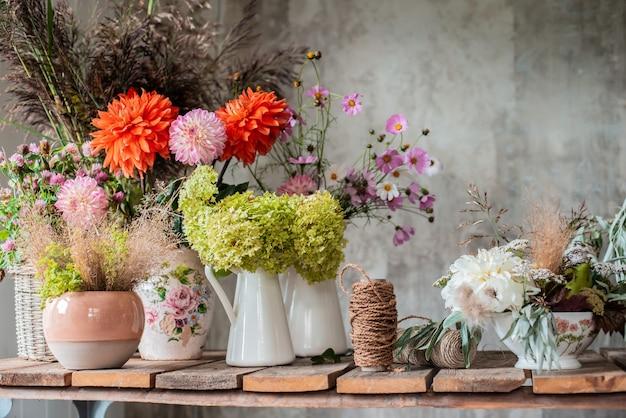 コンクリートの壁の上に女の子の花屋の手でガラスの瓶に白い花の花束。