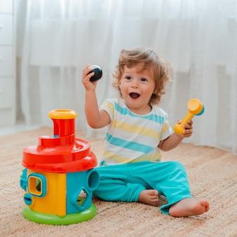 赤ちゃんは、教育用プラスチック玩具で部屋の床で遊ぶ。
