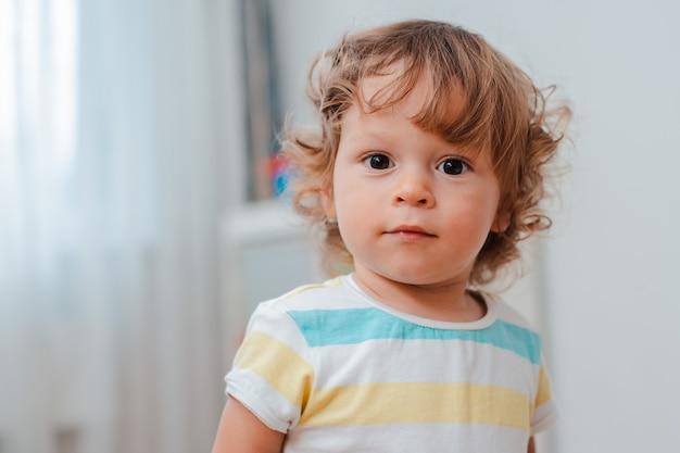 赤ちゃんの顔、巻き毛のかわいい赤ちゃんのクローズアップ。の肖像