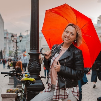 秋の市内中心部で赤い傘の下で若い陽気な女性