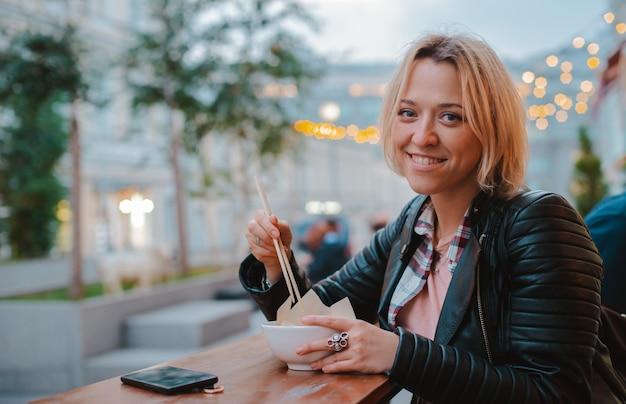 モスクワの木製スティックテーブル通りベトナムカフェでご飯フォーボーを食べるヨーロッパのブロンドの女の子。