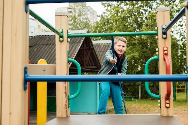 遊び場で少年。ロープ競争。登ります。夏の幸せな子供時代。達成と成功のために努力しています。屋外の遊び場