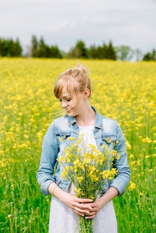 垂直方向の肖像画のヒナギクのフィールドで美しいブロンドの女の子。の花のフィールドに白いドレスを着た女性。ヒナギクの花束を持つ少女。村の夏。野の花。