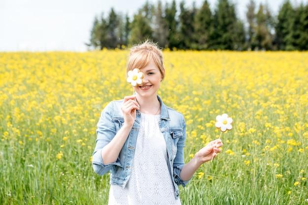 素敵なブロンドの女の子、菜種の開花フィールド。黄色の花、手にカモミールキャンディー、甘い花、目を隠す、彼の顔にそれをもたらした。村の夏の日。自由、空気は風