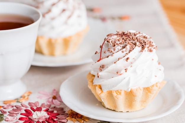 白いウッドの背景にバニラカップケーキ