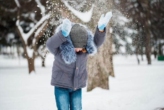 Счастливый мальчик играет в снегу, зимние игры