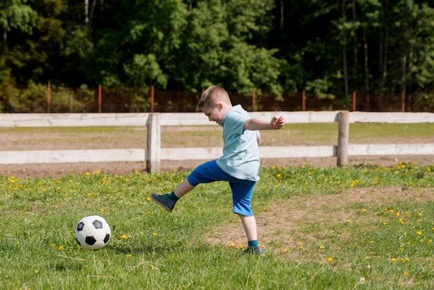 少年は、青いシャツでサッカーをします。