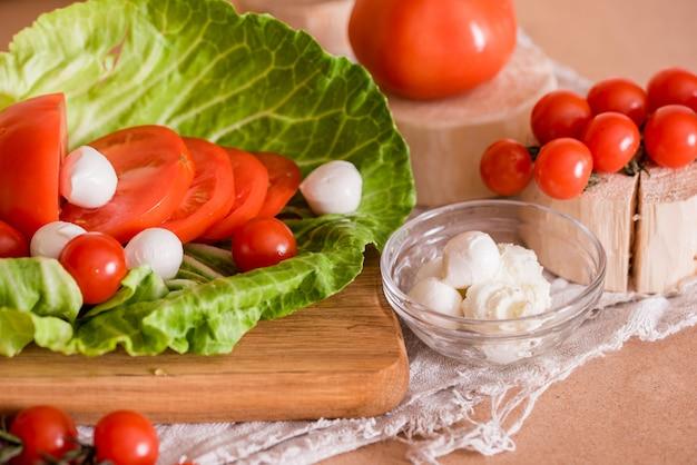 チェリートマト、グリーンキャベツ、ホワイトフェタチーズ、料理、木製のテーブルとまな板の上のサラダ