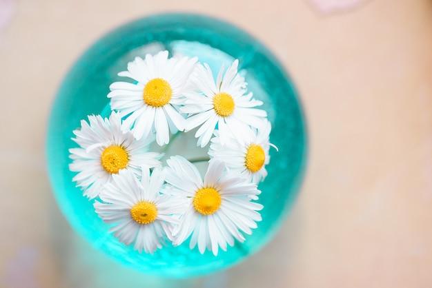 青色の背景に花瓶の夏の花。インテリア装飾