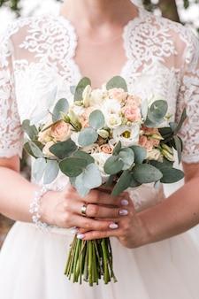 デビッドオースティンの花嫁の手の中のウェディングブーケ