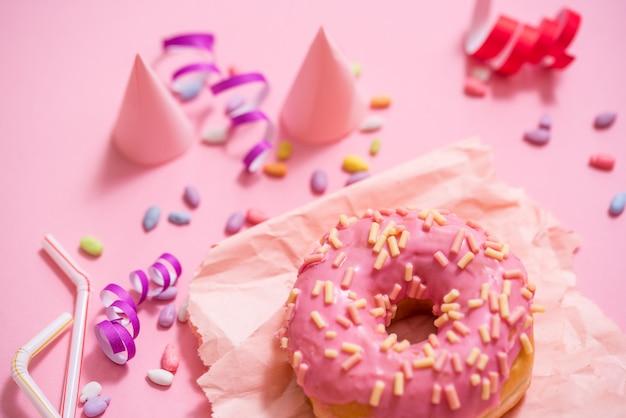 Вечеринка. красочные сладкие круглые глазированные пончики на розовом фоне. праздничная шапка, мишура, конфеты