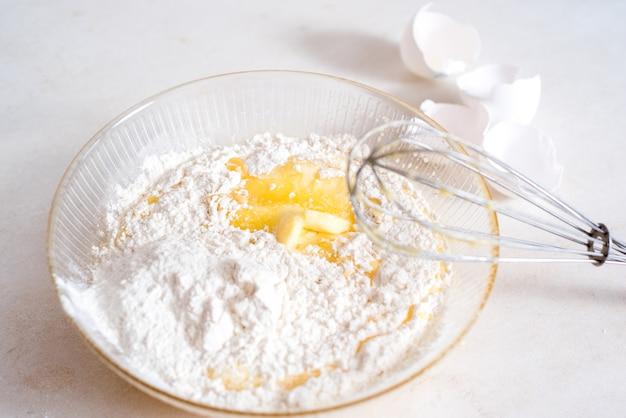 生地の作り方レシピ内の食材の量の測定。生地の成分:小麦粉、卵、麺棒、泡立て器、牛乳、バター、クリーム。