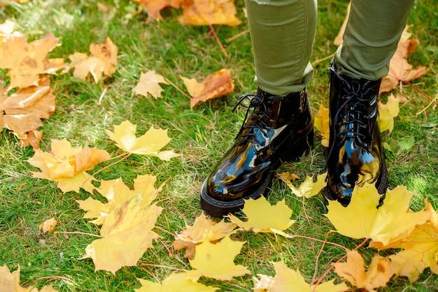 黄色の落ちたカエデの葉のカーペットの上に立っている黒のパテントレザーのブーツで女性の足
