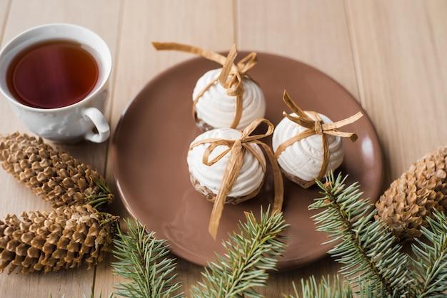 クリスマスのジンジャーブレッド、木製の背景にトウヒの木の枝と熱いお茶のカップ
