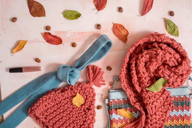 明るい暖かい服、フェルト帽子、ピンクのコンクリート背景に乾燥した黄色の葉で秋の組成物。レディースアクセサリー-バッグ、ネクタイ、財布、口紅。秋のカード