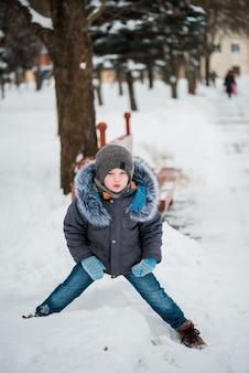 Милый маленький смешной ребенок в красочной зимней одежде, с удовольствием со снегом,