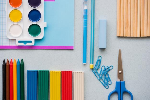 学校の科目のための良い準備。色鉛筆、多色鉛筆、ペーパークリップはさみペン、水彩絵の具の学校の付属品。上面図