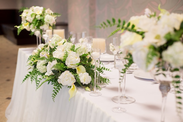 Свадебный декор в интерьере, белые цветы на столе, сервировка стола хрустальными бокалами.