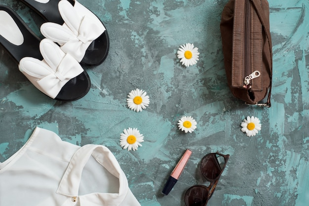 Летний отдых фон, плоские лежал пляжные женские аксессуары: соломенная шляпа, браслеты, кожаные сандалии, солнцезащитные очки, бусы и морские звезды на синем столе.
