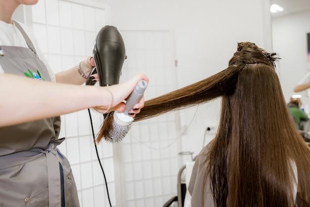 ビューティーサロン、ヘアケアのブルネットの少女。美容師の女性のためのヘアカット、染毛、洗浄。