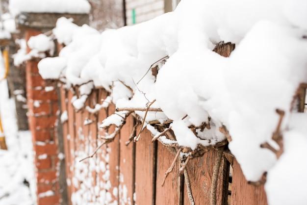 村の冬。木製の冷凍フェンス。雪とつららはどこにでもあります。