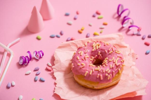 パーティー。カラフルで甘い丸い艶をかけたドーナツ。お祝いキャップ、見掛け倒し、キャンディ
