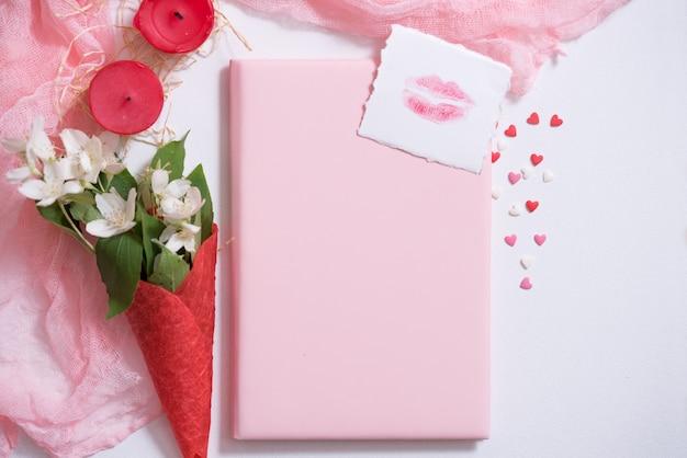 Макет с открыткой и жасмином на розовом фоне. открытка и белые цветы. вафля для мороженого, поцелуй в губы