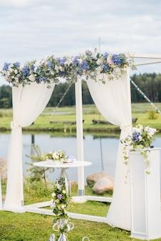 結婚式のアーチは青い花と白い光の絹で飾られています。夏の結婚式