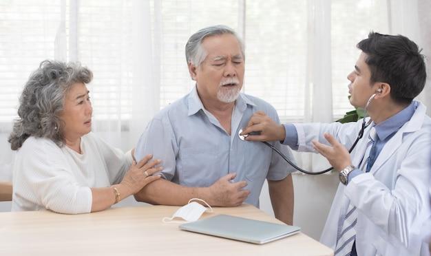 Азиатский старший пожилой старик с маской лежа на диване, в то время как молодой кавказский доктор сидит на колене проверить его сердцебиение
