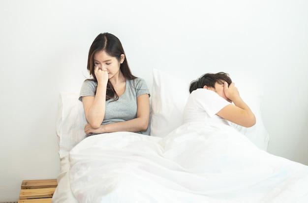 Молодые азиатские пары в кровати имея проблемы и руки мужчины и женщины кризиса покрывают голову с смущенным