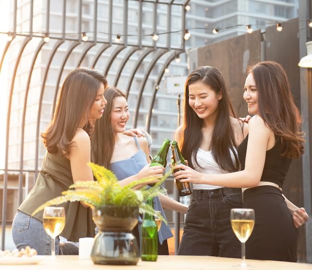 ビールのボトルを保持している幸せなアジアの女性