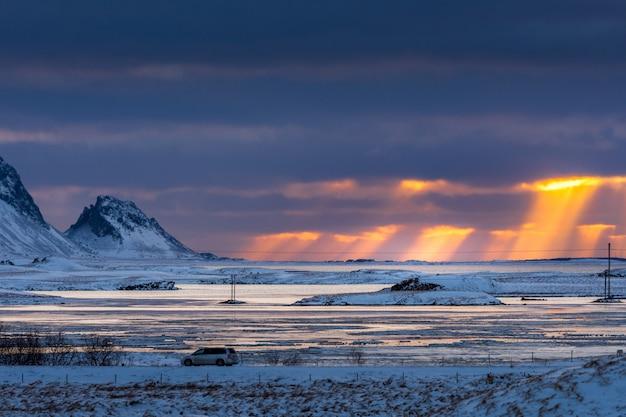美しい風景と曇りの劇的な空と小さな車で朝の日の出。