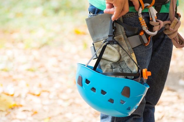 登山用具とヘルメット屋外、上面図を持つ男。顔が見えない