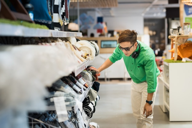 Азиатский мужчина, одетый в непринужденный стиль и надевающий очки и наушники, выбирающие брюки и делающие