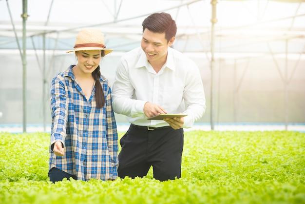 プロのアジア人科学者は、アジアの女性庭師農場で立っている緑の野菜水耕農場の品質をチェックします。