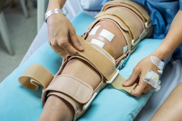 包帯圧縮膝装具を持つ患者は、看護病院のベッドで負傷をサポートします。ヘルスケアおよび医療サポート。