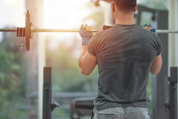 ウェイトトレーニングを持ち上げる強い筋肉アジア男の裏側は、フィットネスジム、スポーツ、健康的な概念で彼の胸を行使します。