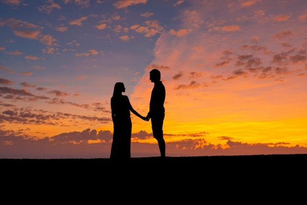 カップルのシルエットが一緒に手を繋いで、ロマンチックな男と女が夕焼け空を背景に。