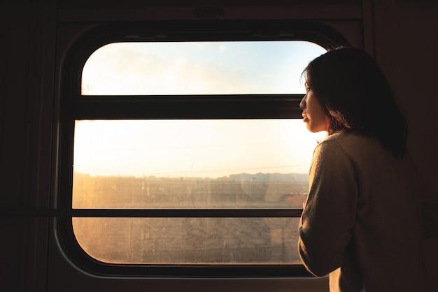Азиатская женщина путешественник смотрит в окно движущегося поезда