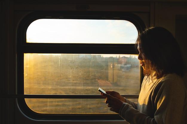 Азиатская женщина путешественник смотрит на смарт-мобильный телефон рядом с окном движущегося поезда