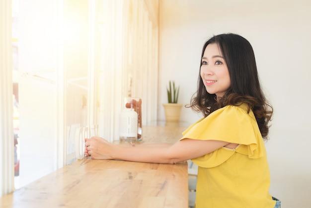 Привлекательная счастливая азиатская женщина сидит в кафе ждать и смотря вне работу окна, студента или фриланс вне офиса.