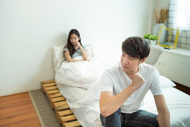 アジアの男性が落ち込んで、不幸な関係を持つ女性は、夫婦の生活の中で社会的な問題を議論した後、ベッドに座っています。