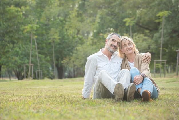 秋の公園で一緒に地面に座っている年配の白人カップル。妻は夫の頭に頭を載せ、男の膝に手を置きます。美しい愛の関係と老人の世話。