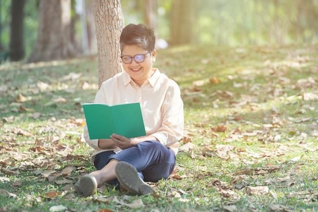 Азиатская старшая старшая женщина прочитала книгу сидит на парке зеленой травы публично с стороной улыбки - концепция старости, выхода на пенсию и людей.
