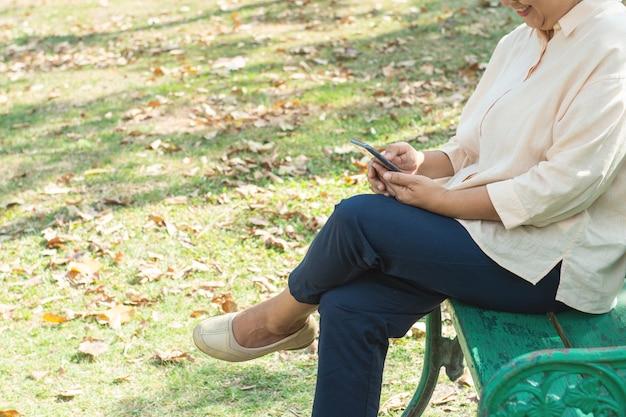 高齢者の女性はベンチに座って、スマートモバイル携帯電話を使用して笑顔で屋外のソーシャルネットワークに接続します。古い女性のテキストメッセージとアプリを使用して。